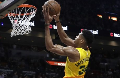 Milwaukee Bucks forward Giannis Antetokounmpo (34) goes up to shoot over Miami Heat guard Dwyane Wade (3) during the second half of an NBA basketball game, Saturday, Dec. 22, 2018, in Miami. (AP Photo/Lynne Sladky)