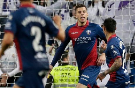 Huesca players, center, celebrate after scoring the opening goal during a Spanish La Liga soccer match between Real Madrid and Huesca at the Santiago Bernabeu stadium in Madrid, Sunday, March 31, 2019. (AP Photo/Bernat Armangue)