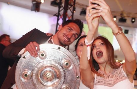 In this May 20, 2017 photo, Bayern soccer player Mats Hummels, left, and his wife Cathy Hummels take a selfie with the Championships trophy during the FC Bayern Munich  Championships party at Postpalast hotel in Munich, Germany. (Alexander Hassenstein/Pool Photo via AP)