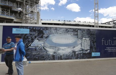 FILE - In this May 14, 2017, file photo, football fans smile as they pass a poster showing the plans for the new stadium, in front of construction work at White Hart Lane stadium in London, before a match between Tottenham Hotspur and Manchester United. The Oakland Raiders will host the Seattle Seahawks in the first NFL game at the new London stadium of English Premier League club Tottenham. The game will be played in week six of the season on Oct. 14. (AP Photo/Frank Augstein, File)