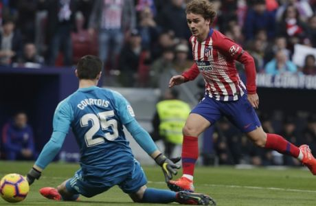 Atletico Madrid's Antoine Griezmann, right shoots past Real Madrid's goalkeeper Thibaut Courtois to score his side's 1st goal during a Spanish La Liga soccer match between Atletico Madrid and Real Madrid at the Metropolitano stadium in Madrid, Spain, Saturday, Feb. 9, 2019. (AP Photo/Manu Fernandez)