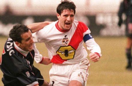 Seville's Bosnian Misrad Hibic, left, falls as he tries to get around Rayo Vallecano's captain Imanol Cota during a Spanish league soccer match in Madrid Sunday January 9 2000. Rayo won the match 2-0. (AP Photo/Zaheeruddin Abdullah)