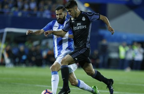 Real Madrid's Marco Asensio vies for the ball with Leganes' Dimitrios Siovas, left, during a Spanish La Liga soccer match between Leganes and Real Madrid at the Butarque stadium in Madrid, Wednesday, April 5, 2017. (AP Photo/Francisco Seco)