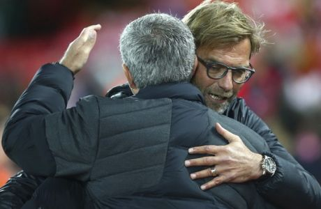 Liverpool's manager Juergen Klopp, right, hugs Manchester United's manager Jose Mourinho ahead of the English Premier League soccer match between Liverpool and Manchester United at Anfield stadium in Liverpool, England, Monday, Oct. 17, 2016. (AP Photo/Dave Thompson)
