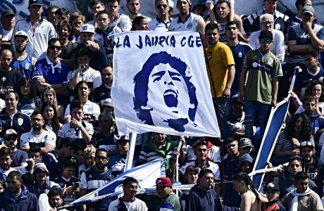 Οπαδοί της Χιμνάσια Λα Πλάτα κρατούν ένα λάβαρο με το πρόσωπο του προπονητή της ομάδας, Ντιέγκο Μαραντόνα, τον Σεπτέμβριο του 2019