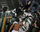 Lazio's Fabio Firmani pays his homage to a giant portrait of Gabriele Sandri, the Lazio supporter who was shot to death by a police officer, at the end of the Italian Top League soccer match beetween Lazio and Parma, at Rome's Olympic  Stadium, Sunday Nov. 25, 2007. Firmani scored the decisive goal that gave his side a 1-0 win over Parma. (AP Photo/Alessandra Tarantino)