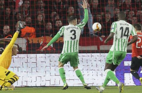 Betis' goalkeeper Joel Robles, left, Betis' Javi García, 2nd left, and Betis' William Carvalho, 2nd right, look at Rennes' Adrien Hunou as he scores the opening goal during the UEFA Europa League round of 32 soccer match between Rennes and Real Betis at Roazhon Park stadium in Rennes, western France, Thursday, Feb. 14, 2019. (AP Photo/David Vincent)