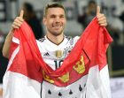 Germany's Lukas Podolski holds a flag of the German city of Cologne after the friendly soccer match between Germany and England in Dortmund, Germany, Wednesday, March 22, 2017. (AP Photo/Martin Meissner)