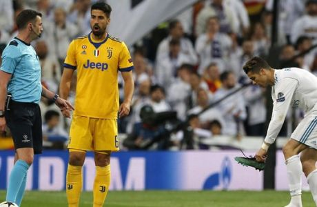 Juventus' Sami Khedira, center talks to Referee Michael Oliver as Real Madrid's Cristiano Ronaldo puts his shoe on during a Champions League quarter-final, 2nd leg soccer match between Real Madrid and Juventus at the Santiago Bernabeu stadium in Madrid, Spain, Wednesday, April 11, 2018. (AP Photo/Paul White)