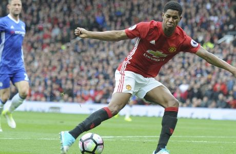 Manchester United's Marcus Rashford shoots to score his side's first goal during the English Premier League soccer match between Manchester United and Chelsea at Old Trafford stadium in Manchester, Sunday, April 16, 2017.(AP Photo/ Rui Vieira)