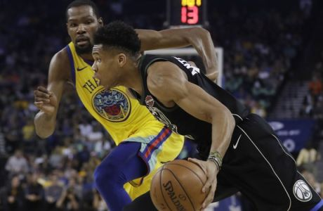 Milwaukee Bucks' Giannis Antetokounmpo, right, dribbles past Golden State Warriors' Kevin Durant during the first half of an NBA basketball game Thursday, March 29, 2018, in Oakland, Calif. (AP Photo/Marcio Jose Sanchez)