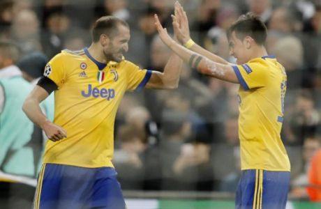 Juventus' Paulo Dybala , right, celebrates with his teammate Giorgio Chiellini after scoring his side second goal during the Champions League, round of 16, second-leg soccer match between Juventus and Tottenham Hotspur, at the Wembley Stadium in London, Wednesday, March 7, 2018. (AP Photo/Frank Augstein)