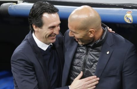 PSG coach Unai Emery, left, chats with Real Madrid coach Zinedine Zidane before the start of the Champions League soccer match, round of 16, 1st leg between Real Madrid and Paris Saint Germain at the Santiago Bernabeu stadium in Madrid, Spain, Wednesday, Feb. 14, 2018. (AP Photo/Paul White)