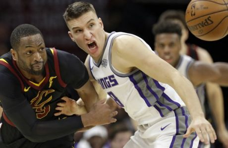 Cleveland Cavaliers' Dwyane Wade, left, and Sacramento Kings' Bogdan Bogdanovic, from Serbia, battle for a loose ball in the second half of an NBA basketball game, Wednesday, Dec. 6, 2017, in Cleveland. The Cavaliers won 101-95. (AP Photo/Tony Dejak)