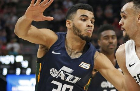 San Antonio Spurs guard Derrick White (4) drives around Utah Jazz guard Naz Mitrou-Long (30) during the second half of an NBA summer league basketball game, Monday, July 2, 2018, in Salt Lake City. (AP Photo/Rick Bowmer)
