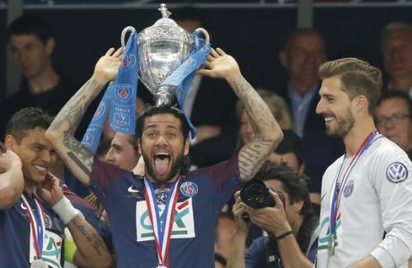 PSG's Dani Alves, left, holds the trophy a he jokes while his teammate goalkeeper Kevin Trapp looks on during the French Cup soccer final between Les Herbiers and Paris Saint Germain at the Stade de France stadium in Saint-Denis, outside Paris, Tuesday, May 8, 2018. (AP Photo/Michel Euler)