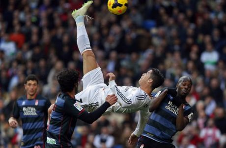FILE - In this Saturday, Jan. 25, 2014 file photo Real Madrid's Cristiano Ronaldo, of Portugal, top, tries to score in between opposition players during a Spanish La Liga soccer match between Real Madrid and Granada at the Santiago Bernabeu stadium in Madrid, Spain. (AP Photo/Andres Kudacki, File)