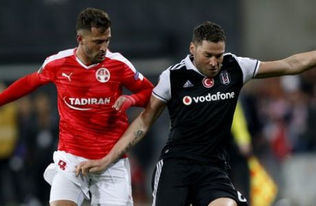 Besiktas Dusko Tosic, right, and Hapoel Beersheba Mohamed Ghadir fight for the ball during the Europa League round of 32, first leg, soccer match in Beersheba, Israel, Thursday, Feb. 16, 2017. (AP Photo/Ariel Schalit)