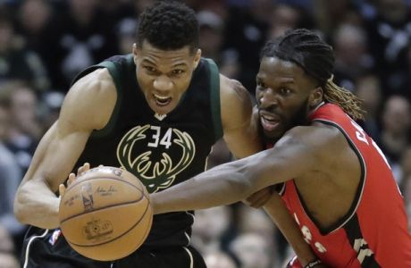Toronto Raptors' DeMarre Carroll and Milwaukee Bucks' Giannis Antetokounmpo go after a loose ball during the second half of game 3 of their NBA first-round playoff series basketball game Thursday, April 20, 2017, in Milwaukee. The Bucks won 106-77. (AP Photo/Morry Gash)