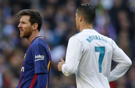 Real Madrid's Cristiano Ronaldo, right, runs by Barcelona's Lionel Messi during the Spanish La Liga soccer match between Real Madrid and Barcelona at the Santiago Bernabeu stadium in Madrid, Spain, Saturday, Dec. 23, 2017. (AP Photo/Paul White)