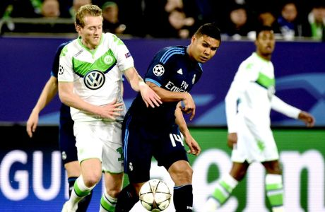 """Wolfsburg's striker Andre Schuerrle (L) and Real Madrid's Brazilian midfielder Casemiro vie for the ball during the UEFA Champions League quarter-final, first-leg football match between VfL Wolfsburg and Real Madrid on April 6, 2016 in Wolfsburg, northern Germany.  / AFP / John MACDOUGALL        (Photo credit should read JOHN MACDOUGALL/AFP/Getty Images)"""