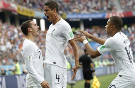 France's Kylian Mbappe, right, and Antoine Griezmann celebrate after Raphael Varane, center scored his side's first goal during the quarterfinal match between Uruguay and France at the 2018 soccer World Cup in the Nizhny Novgorod Stadium, in Nizhny Novgorod, Russia, Friday, July 6, 2018. (AP Photo/Petr David Josek)