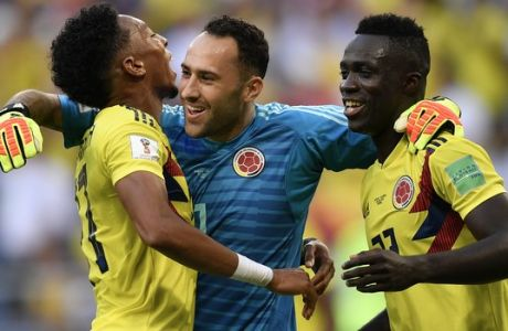 Colombia goalkeeper David Ospina, center, celebrates with teammates Johan Mojica, left, and Davinson Sanchez, right,the end of the group H match between Senegal and Colombia, at the 2018 soccer World Cup in the Samara Arena in Samara, Russia, Thursday, June 28, 2018. (AP Photo/Martin Meissner)