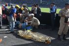 TOPSHOT - EDITORS NOTE: Graphic content / Rescue workers assist an injured fan of Honduran team Motagua next to the body of one of two supporters of the team who were killed in a stampede at the National Stadium in Tegucigalpa on May 28, 2017. At least two people were killed and 25 injured in the chaos and unrest caused when hundreds of fans tried to enter the overcrowded stadium before the final match of the Clausura football tournament between Motagua and Honduras Progreso. / AFP PHOTO / ORLANDO SIERRA        (Photo credit should read ORLANDO SIERRA/AFP/Getty Images)