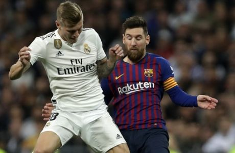 Real midfielder Toni Kroos, left, and Barcelona forward Lionel Messi challenge for the ball during the Copa del Rey semifinal second leg soccer match between Real Madrid and FC Barcelona at the Bernabeu stadium in Madrid, Wednesday, Feb. 27, 2019. (AP Photo/Manu Fernandez)
