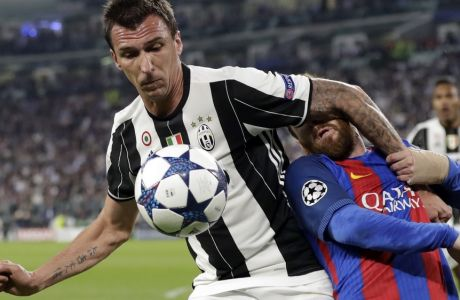 Juventus's Mario Mandzukic, left, and Barcelona's Lionel Messi vie for the ball during a Champions League, quarterfinal, first-leg soccer match between Juventus and Barcelona, at the Juventus Stadium in Turin, Italy, Tuesday, April 11, 2017. (AP Photo/Antonio Calanni)