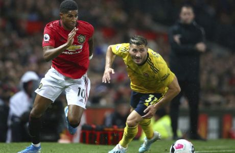 Manchester United's Marcus Rashford, left, vies for the ball with Arsenal's Sead Kolasinac during the English Premier League soccer match between Manchester United and Arsenal at Old Trafford in Manchester, England, Monday, Sept. 30, 2019. (AP Photo/Dave Thompson)