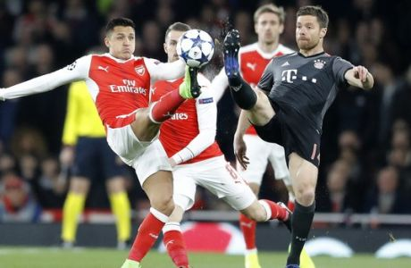 Arsenal's Alexis Sanchez, left, and Bayern's Xabi Alonso battle for the ball during the Champions League round of 16 second leg soccer match between Arsenal and Bayern Munich at the Emirates Stadium in London, Tuesday, March 7, 2017. (AP Photo/Frank Augstein)
