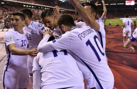 Greek players celebrate after Greece's Kostas Mitroglou scored the match's first goal during the Euro 2018 Group H qualifying match between Belgium and Greece at the King Baudouin stadium in Brussels on Saturday, March 25, 2017. (AP Photo/Geert Vanden Wijngaert)