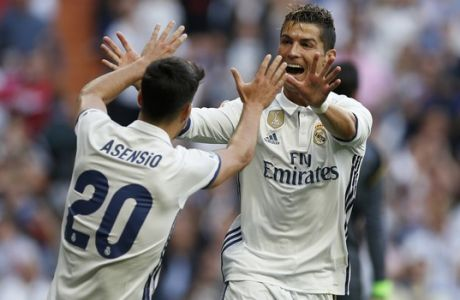 Real Madrid's Cristiano Ronaldo, right, celebrates with teammate Marco Asensio after scoring their side's second goal against Sevilla during the La Liga soccer match between Real Madrid and Sevilla at the Santiago Bernabeu stadium in Madrid, Sunday, May 14, 2017. (AP Photo/Francisco Seco)