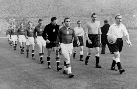 The teams coming out, led by the two captains, Billy Wright of England, right, and Ferenc Puskas of Hungary.