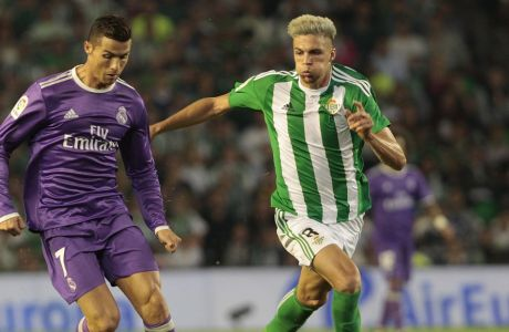 Real Madrid's Cristiano Ronaldo, left, and Betis' Jonas Martin, right, fight for the ball during their La Liga soccer match at the Benito Villamarin stadium, in Seville, Spain on Saturday, Oct. 15, 2016. (AP Photo/Angel Fernandez)