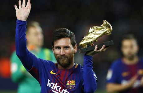FC Barcelona's Lionel Messi holds up the Golden Shoe award, as the last season's leading goalscorer in league matches from the top division of every European national league, prior of the Spanish La Liga soccer match between FC Barcelona and Deportivo Coruna at the Camp Nou stadium in Barcelona, Spain, Sunday, Dec. 17, 2017. (AP Photo/Manu Fernandez)
