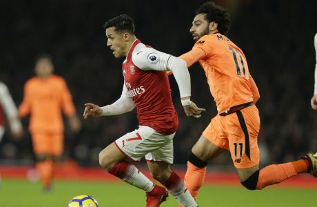 Arsenal's Alexis Sanchez, left vies for the ball with Liverpool's Mohamed Salah during their English Premier League soccer match between Arsenal and Liverpool at the Emirates stadium London, Friday, Dec. 22, 2017. (AP Photo/Alastair Grant)