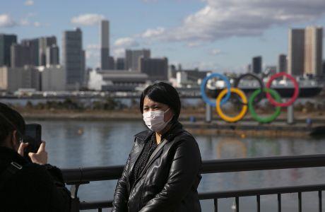 Μία τουρίστας φοράει μάσκα για προστασία από τον κορονοϊό μπροστά από τους ολυμπιακού κύκλους στην περιοχή Οντάιμπα του Τόκιο, Τετάρτη 29 Ιανουαρίου 2020