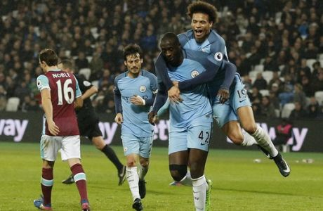 Manchester City's Leroy Sane jumps onto Manchester City's Yaya Toure after he scores a goal during the English Premier League soccer match between West Ham and Manchester City at the London stadium, Wednesday, Feb. 1, 2017. (AP Photo/Frank Augstein)