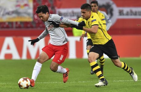 Salzburg's Takumi Minamino, left, and Vitoria's Guillermo Celis challenge for the ball during the Europa League group I soccer match between FC Salzburg and Vitoria SC in the Arena in Salzburg, Austria, Thursday, Nov. 23, 2017. (AP Photo/Kerstin Joensson)