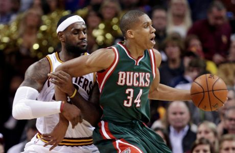 Cleveland Cavaliers' LeBron James, left, and Milwaukee Bucks' Giannis Antetokounmpo (34), from Greece, get tangled up in the first quarter of an NBA basketball game Tuesday, Dec. 2, 2014, in Cleveland. (AP Photo/Tony Dejak)