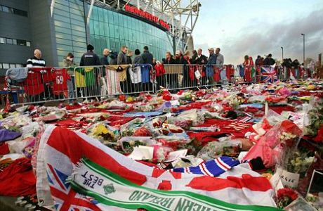 Football fans looks at shirts, scarves and flowers left as tributes to ex-footballer George Best outside Manchester United's stadium at Old Trafford in Manchester, 03 December 2005.  Thousands of fans paid their respects to Best on Saturday at his funeral at Stormont Parliament buildings in Belfast, Northern Ireland. AFP PHOTO/ADRIAN DENNIS  (Photo credit should read ADRIAN DENNIS/AFP/Getty Images)