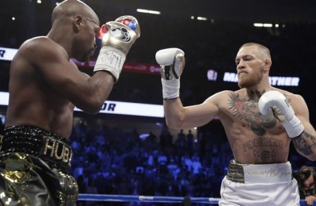 Floyd Mayweather Jr., left, fights Conor McGregor in a super welterweight boxing match Saturday, Aug. 26, 2017, in Las Vegas. (AP Photo/Isaac Brekken)