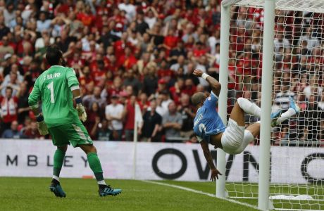 Manchester City's Kyle Walker leaps and clears the ball of the line from a shot by Liverpool's Mohamed Salah during the Community Shield soccer match between Manchester City and Liverpool at Wembley Stadium in London, Sunday, Aug. 4, 2019. (AP Photo/Frank Augstein)