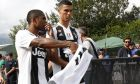 Juventus' Cristiano Ronaldo, right, talks with his teammate Douglas Costa prior to the start of a friendly soccer match between the Juventus A and B teams, in Villar Perosa, near Turin, Italy, Sunday, Aug.12, 2018. (AP Photo/Antonio Calanni)