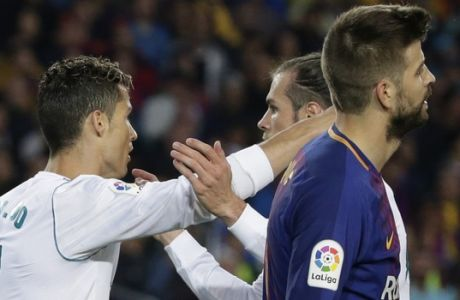 Real Madrid's Gareth Bale, rear right, congratulates Real Madrid's Cristiano Ronaldo, left, who scored his side's first goal as Barcelona's Gerard Pique, right, failed to stop the shot during a Spanish La Liga soccer match between Barcelona and Real Madrid, dubbed 'El Clasico', at the Camp Nou stadium in Barcelona, Spain, Sunday, May 6, 2018. (AP Photo/Emilio Morenatti)