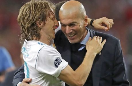 Real Madrid coach Zinedine Zidane, right, celebrates with Luka Modric after winning the Champions League Final soccer match between Real Madrid and Liverpool at the Olimpiyskiy Stadium in Kiev, Ukraine, Saturday, May 26, 2018. (AP Photo/Sergei Grits)