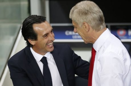 PSG head coach Unai Emery, left, greets Arsenal manager Arsene Wenger prior to the Champions League group A soccer match group between Paris Saint Germain and Arsenal at the Parc des Princes stadium in Paris, Tuesday, Sept. 13, 2016. (AP Photo/Francois Mori)