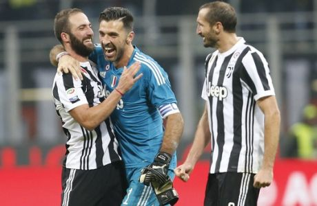 Juventus' Gonzalo Higuain, left, celebrates with teammates goalkeeper Gianluigi Buffon, centre and Giorgio Chiellini after the end of the Serie A soccer match between AC Milan and Juventus, at the Milan San Siro stadium, Italy, Saturday, Oct. 28, 2017. Juventus won the game 2-0, Higuain scored both goals. (AP Photo/Antonio Calanni)